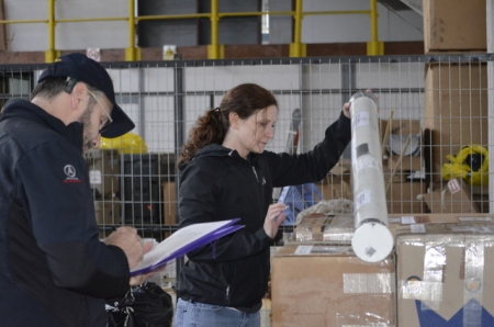 Ronald Ross and Jennifer Bohlander locate and inspect cargo items in the DAMCO warehouse that they had shipped to Punta Arenas over the past couple of months.